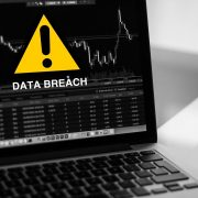 Data breach on laptop with warning sign